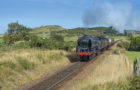 Steam train and carriages, passing through golfcourse with seaside town in background, North Norfolk Railway, Sheringham, Norfolk, England, August